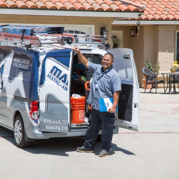 Mauzy technician posing next to company van at a customer's house