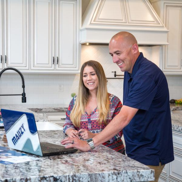 Mauzy comfort advisor discussing with a homeowner at the kitchen table