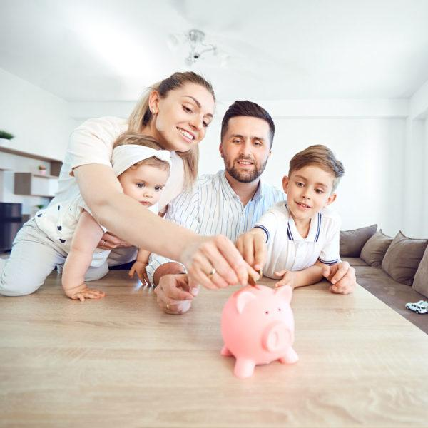 happy family putting change into a piggy bank