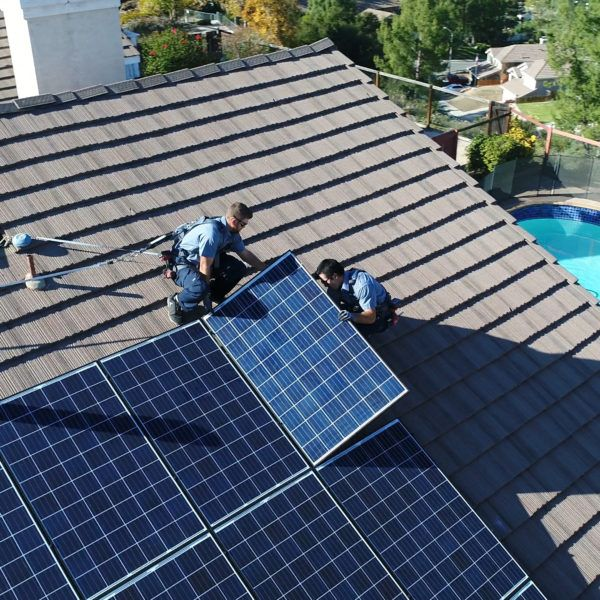 Two Mauzy technicians on the roof of a house installing a solar panel