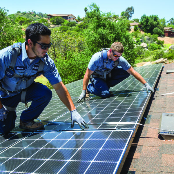 Two Mauzy technicians installing solar panels on the roof of a customer's home