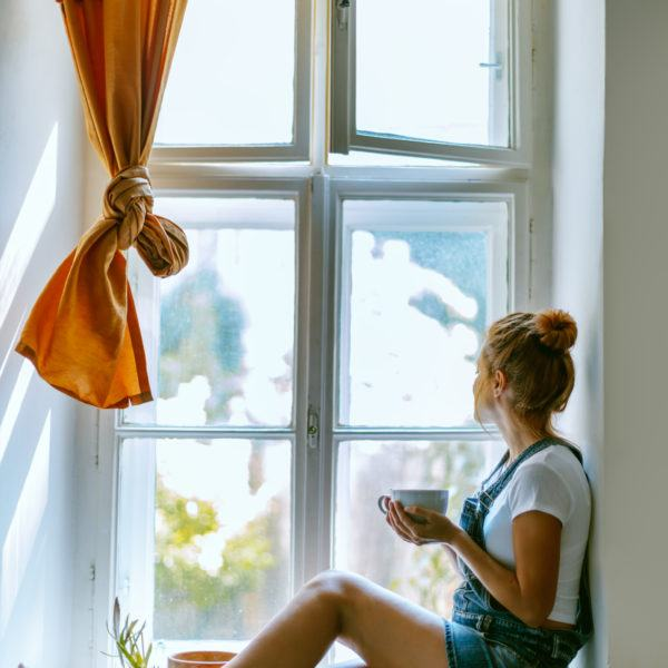 woman sitting and looking outside a window while holding a cup of coffee