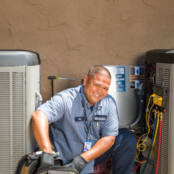 mauzy technician crouching next to air conditioning units doing maintenance
