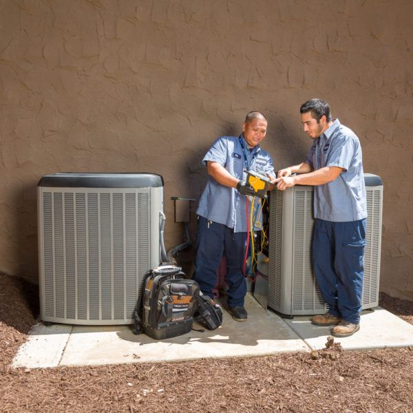 Two Mauzy technicians doing repairs and standing beside two air conditioning units
