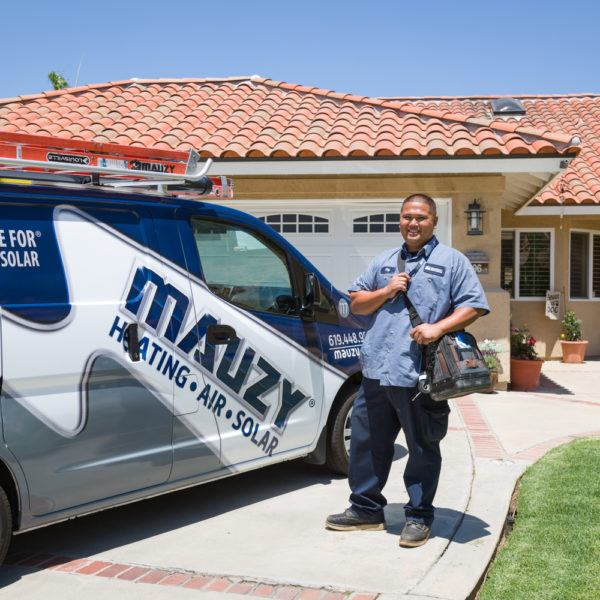 Mauzy technician posing next to van in front of customer's home for a heating repair